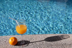 Glass of tasty orange juice standing on the brink of pool  Stock Footage