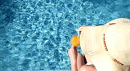 Woman in summer hat drinking cocktail by the pool, top view Stock Footage