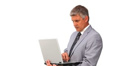 Middle aged man in suit standing with a laptop Stock Footage