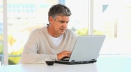 Stock Video Footage of Casual middle aged man working on a laptop