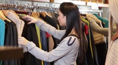 Female looking in clothes shop at dresses - stock footage