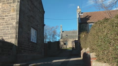 Steps between stone cottages to ancient village church in Norman style, Stock Footage