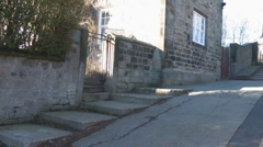 Pan across steps to stone cottage and zoom in to ancient village church Stock Footage