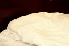 Portrait of smiling woman in bed looking under the blanket, slow motion Stock Footage
