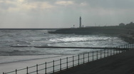 Stock Video Footage of Winter sun light on silvery waves, silhouetted promenade railing and lighthouse