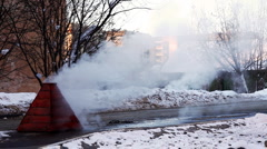 Steam on winter street from water system Stock Footage