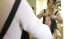 Hairdresser styling hair and walking customer to the till to pay Stock Footage