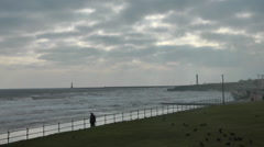 Lone figure walks along seafront promenade on a very windy winter day Stock Footage