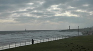 Stock Video Footage of Lone figure walks along seafront promenade on a very windy winter day