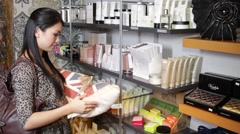 Female looking in gift shop at pillows Stock Footage