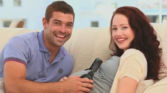 Smiling couple letting their future baby listening to music Stock Footage