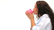 Relaxed woman kissing her piggy bank Stock Footage