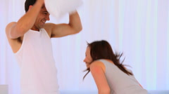 Happy couple playing with pillows - stock footage
