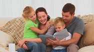 Family reading a children book on their couch Stock Footage