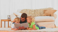 Attentive father reading a children book for his children - stock footage