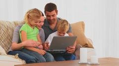 Familly looking at their laptop on the sofa Stock Footage
