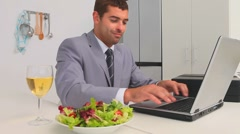 Businessman working on his laptop while he is eating Stock Footage