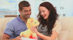 Man offering  a cuddly toy to his wife Stock Footage