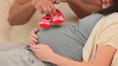 Future parents holding little red shoes Stock Footage