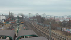 Electric train leaves station heading into the city from bridge over railway Stock Footage