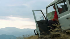 Man in the jeep suv use a map for orientation on the mountain Stock Footage