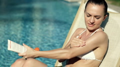 Attractive woman in bikini on sunbed applying sunscreen lotion Stock Footage