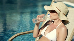 Woman in summer hat lying on sunbed and drinking water by the pool Stock Footage
