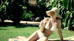 Sexy woman in summer hat and white bikini drinking water Stock Footage