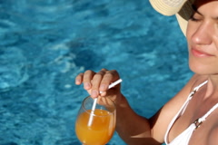 Attractive sexy woman in summer hat drinking exotic drink by the pool Stock Footage