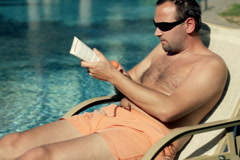 Man on sunbed by the pool applies sunscreen on his arm Stock Footage