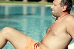 Young handsome man sunbathing by the pool  Stock Footage