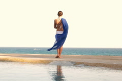 Woman in bikini with waving blue sarong looking out to the sea, slow motion Stock Footage