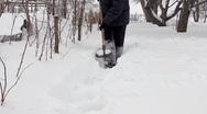 Man shoveling mass of snow in winter garden Stock Footage