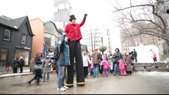 Stilt walker  playing with kids   Stock Footage