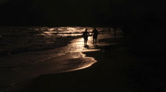 People walk on the beach at sunset Stock Footage