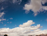 Stock Video Footage of 2K film 24p Winter clouds puff in a crisp deep blue sky in timelapse