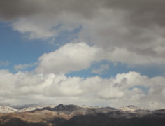 2K Film format - The end of a winter storm passes over snow capped mountains Stock Footage