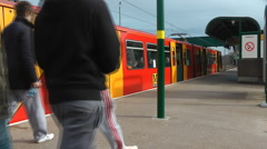 Brightly coloured electric train departs station platform youths walk by Stock Footage