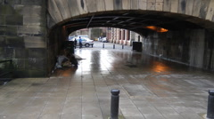 Beneath city centre bridge on wet riverside walk way Stock Footage