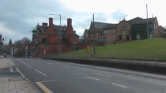 Urban street with old red brick pub, new flats and grassy bank Stock Footage