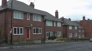 Stock Video Footage of Terrace of 1950's style red brick houses pan to Tower Blocks