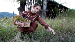 Woman picking flowers in old dress Stock Footage