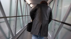 Man walks along narrow corridor with glass walls Stock Footage
