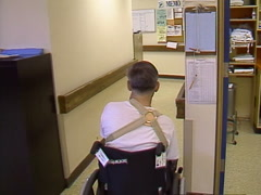 Man in wheelchair trying to make his way down the hall Stock Footage