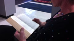 Woman reads book in waiting area Stock Footage