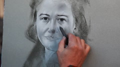 Street painter draws charcoal on canvas portrait of girl Stock Footage