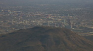 Stock Video Footage of Aerial view from behind A mountain into downtown Tucson