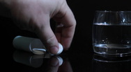 Stock Video Footage of hand of man throws an aspirin into a glass of water. slider shot.