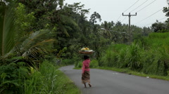 A Balinese Woman Carrying a Basket of Fruit On Her Head, Bali, Indonesia Stock Footage