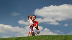Mother and daughter squat on meadow embracing Stock Footage
